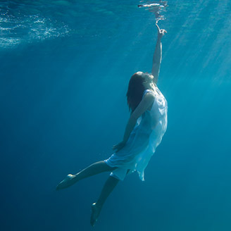 Woman underwater touching surface
