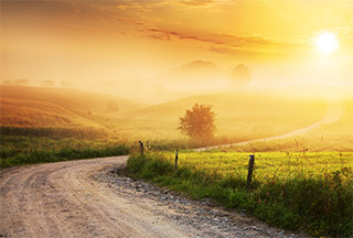 Winding country road at sunset