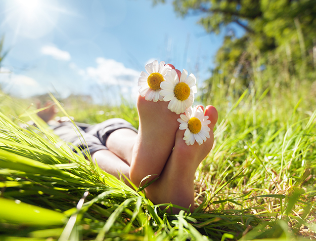Daisies in the toes of a woman lying on the grass
