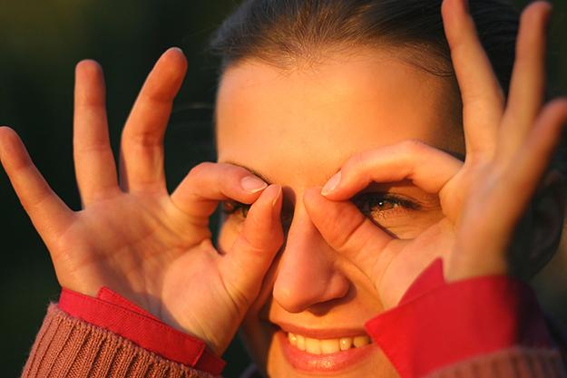 Woman looking through fingers like binoculars